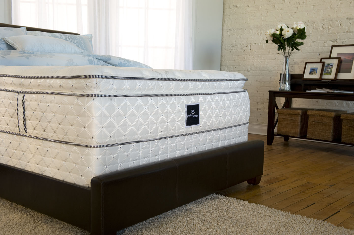 Comfortable Serta Perfect Sleeper Mattress On Espresso Leather Bed Plus Rug On Wooden Floor Matched With Brick Wall For Bedroom Decor Ideas