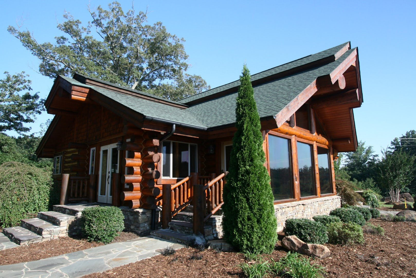 Custom exterior design of Southland Log Homes with glass door and staircase plus pine tree ideas
