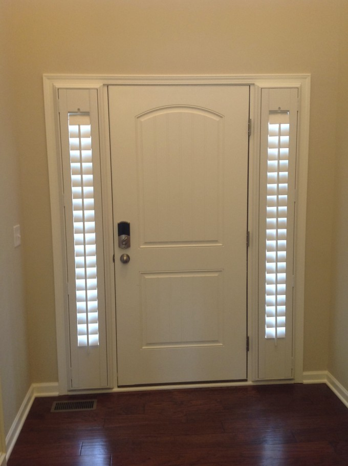 Entry Door Sidelight With Sunburst Shutters On Cream Wall Matched With Brown Tile Floor For Home Interior Design Ideas