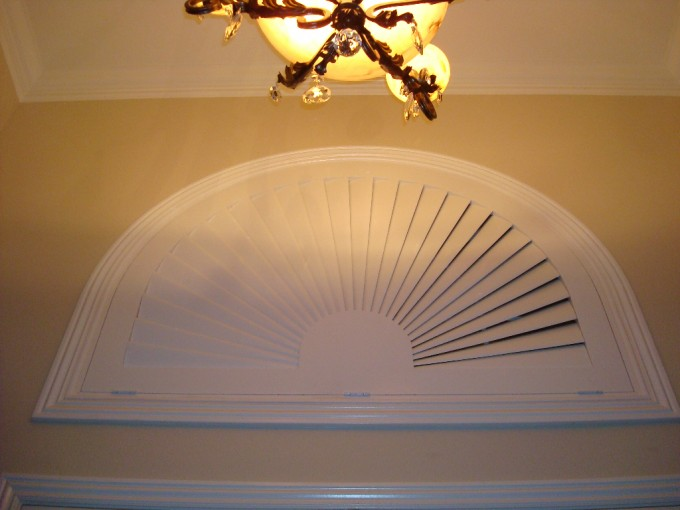 Faux Wood Arch Sunburst Shutters On Cream Wall Matched With White Ceiling With Chandelier For Home Interior Design Ideas