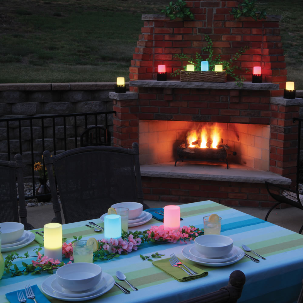 flameless candles with timer on dining table near the outdoor fireplace for outdoor dining ideas