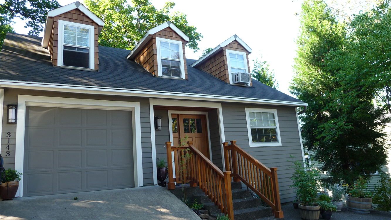 great hardie plank siding in gray with white trim board and gray garage door plus brown wooden railing for home exterior design ideas