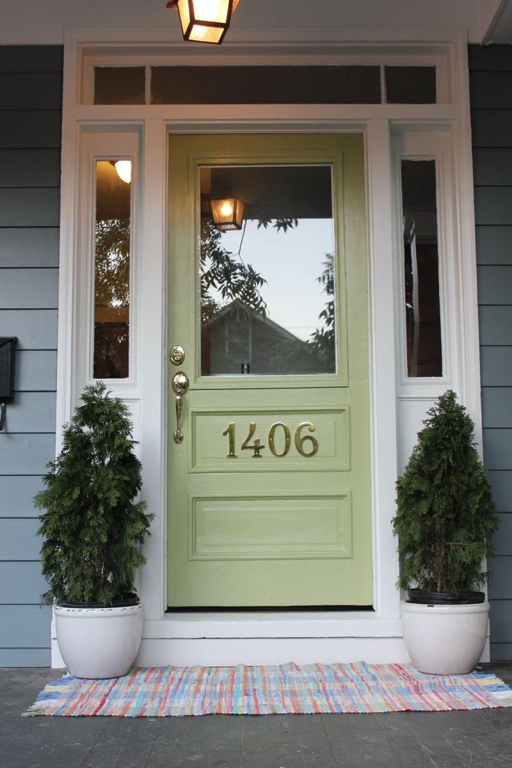 green wooden door with decorative white trim board door on gray horizontal hardie plank siding for home exterior design ideas
