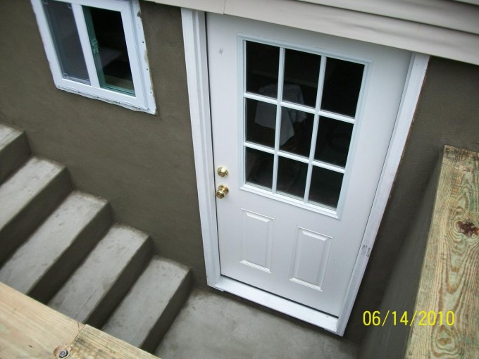 Home Exterior Design With White Wooden Bilco Doors Matched On Gray Cement Siding With White Window Ideas