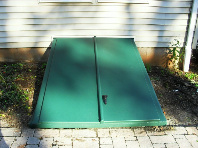 Interesting Cellar Bilco Doors In Green With Black Handle Before The White Horizontal Siding For Home Exterior Design Ideas