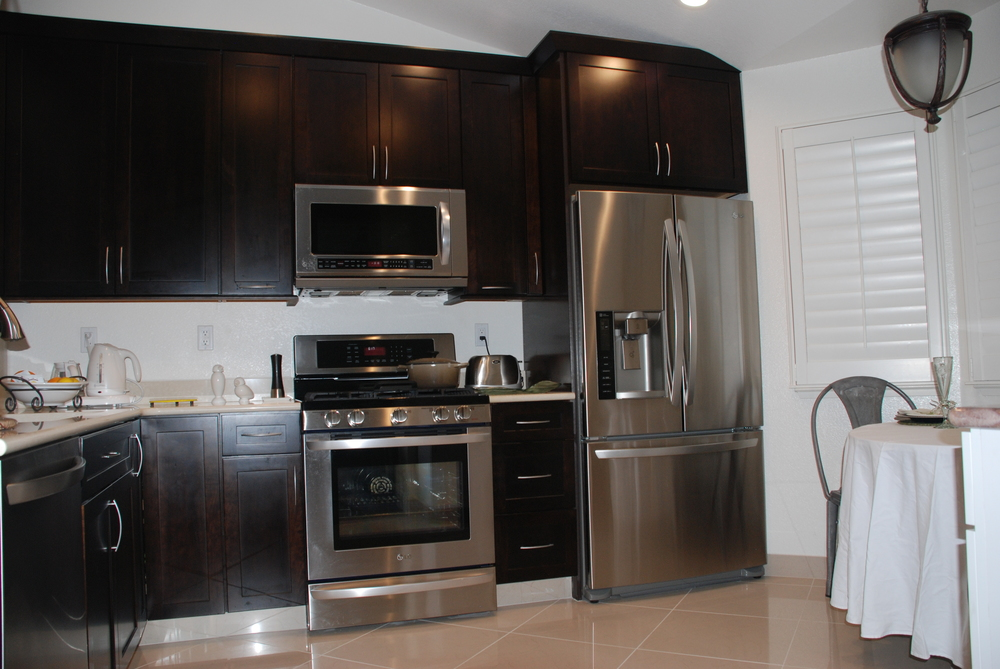 interesting kitchen American Woodmark Cabinets in espresso with white countertop and stove plus fridge on beige tile floor for kitchen decor ideas