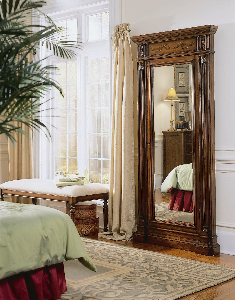 luxury wooden standing mirror jewelry armoire in golden brown on wooden floor before the white wall with wainscoting plus bench for bedroom decor ideas