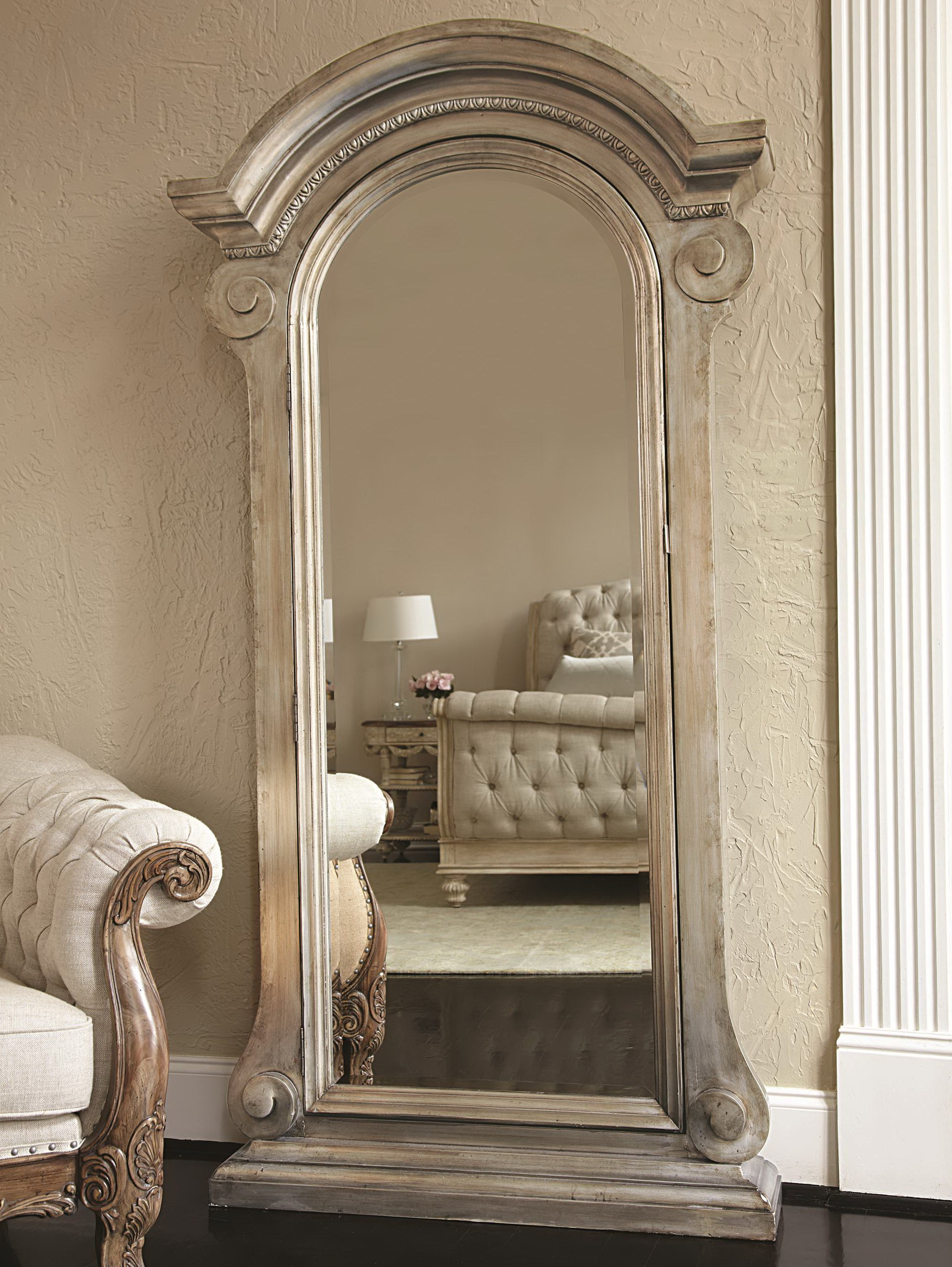 luxury wooden standing mirror jewelry armoire in silver with curve at top before the beige wall for living room decor ideas