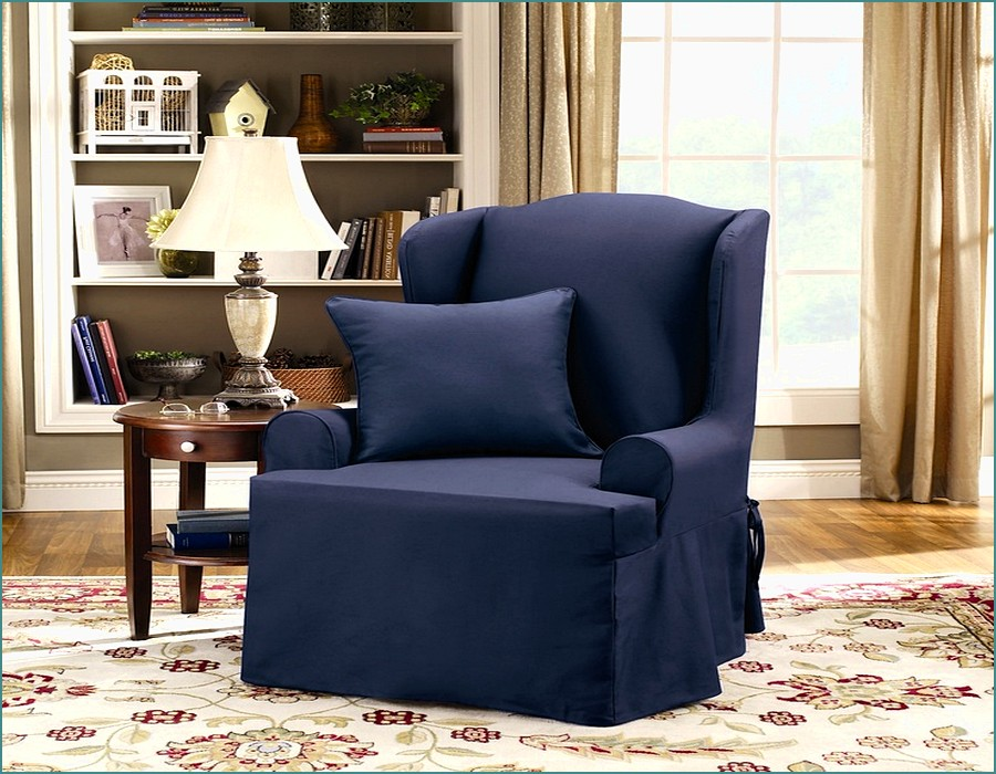 Single Sofa With Navy Wingback Chair Slipcover On Floral Carpet Plus Nightstand And Table Standing Lamp Plus Book Rack For Living Room Decor Ideas