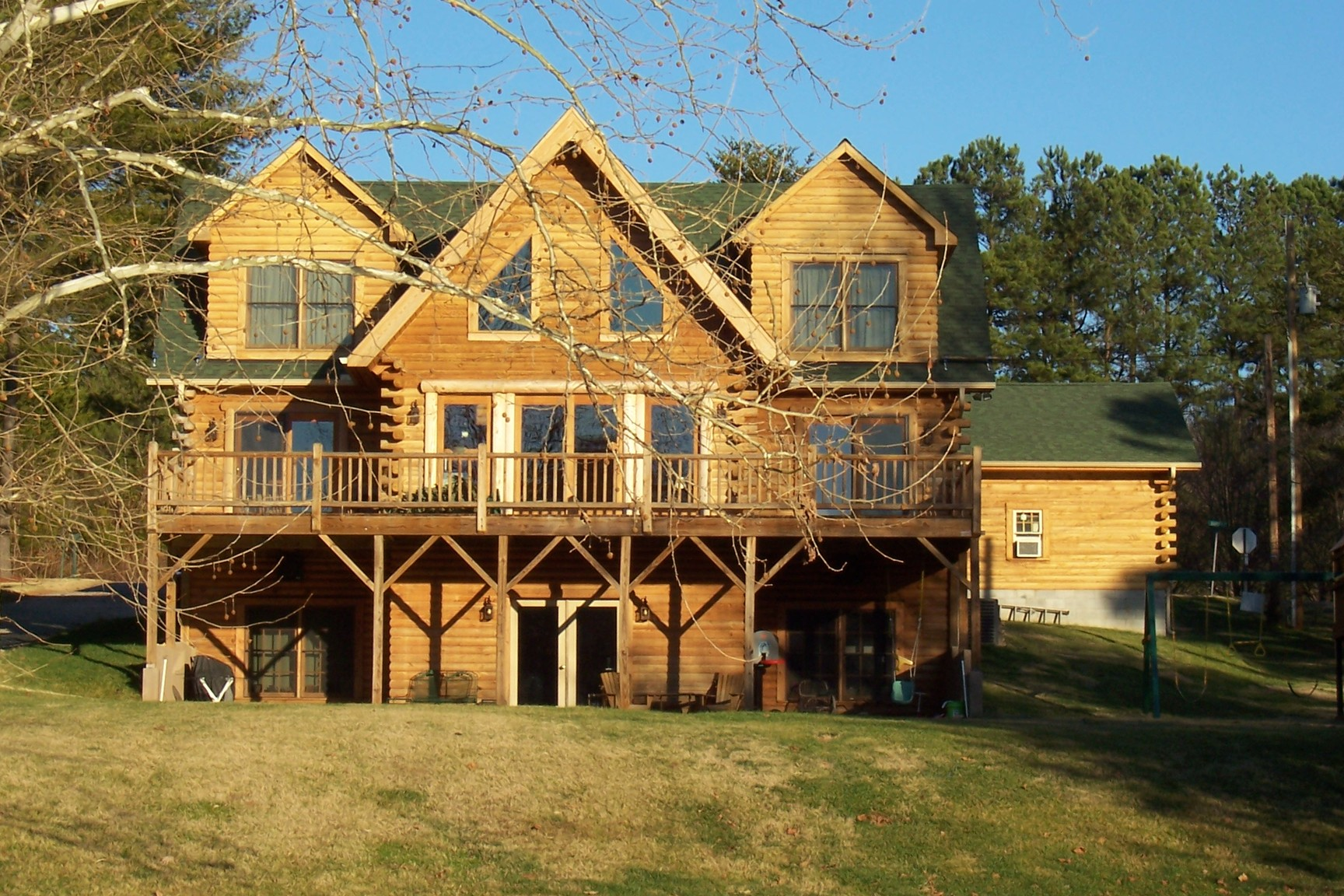 wonderful exterior design of Southland Log Homes with green roof and single hung windows and door plus railing ideas