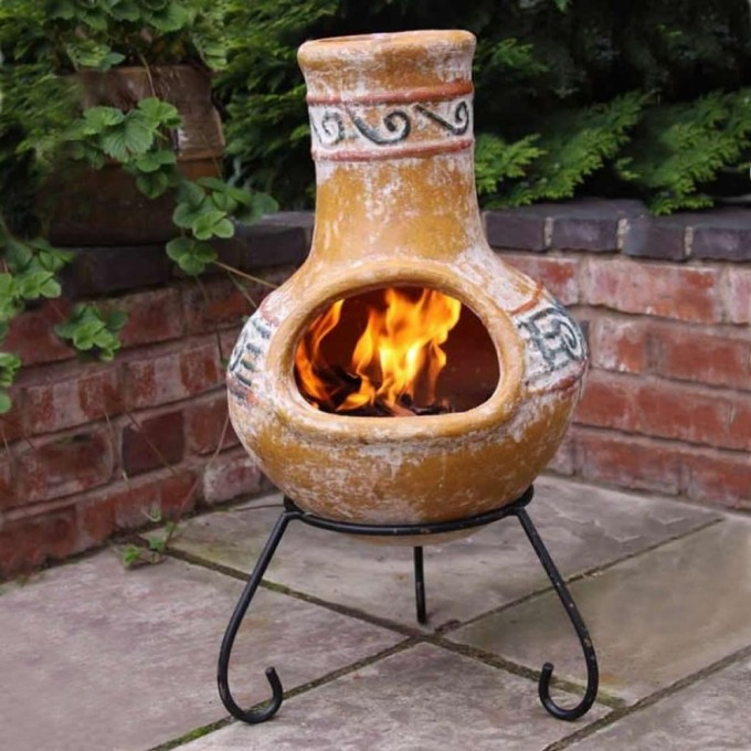Charming Yellow Clay Chiminea With Black Iron Stand For Outdoor Furniture Ideas