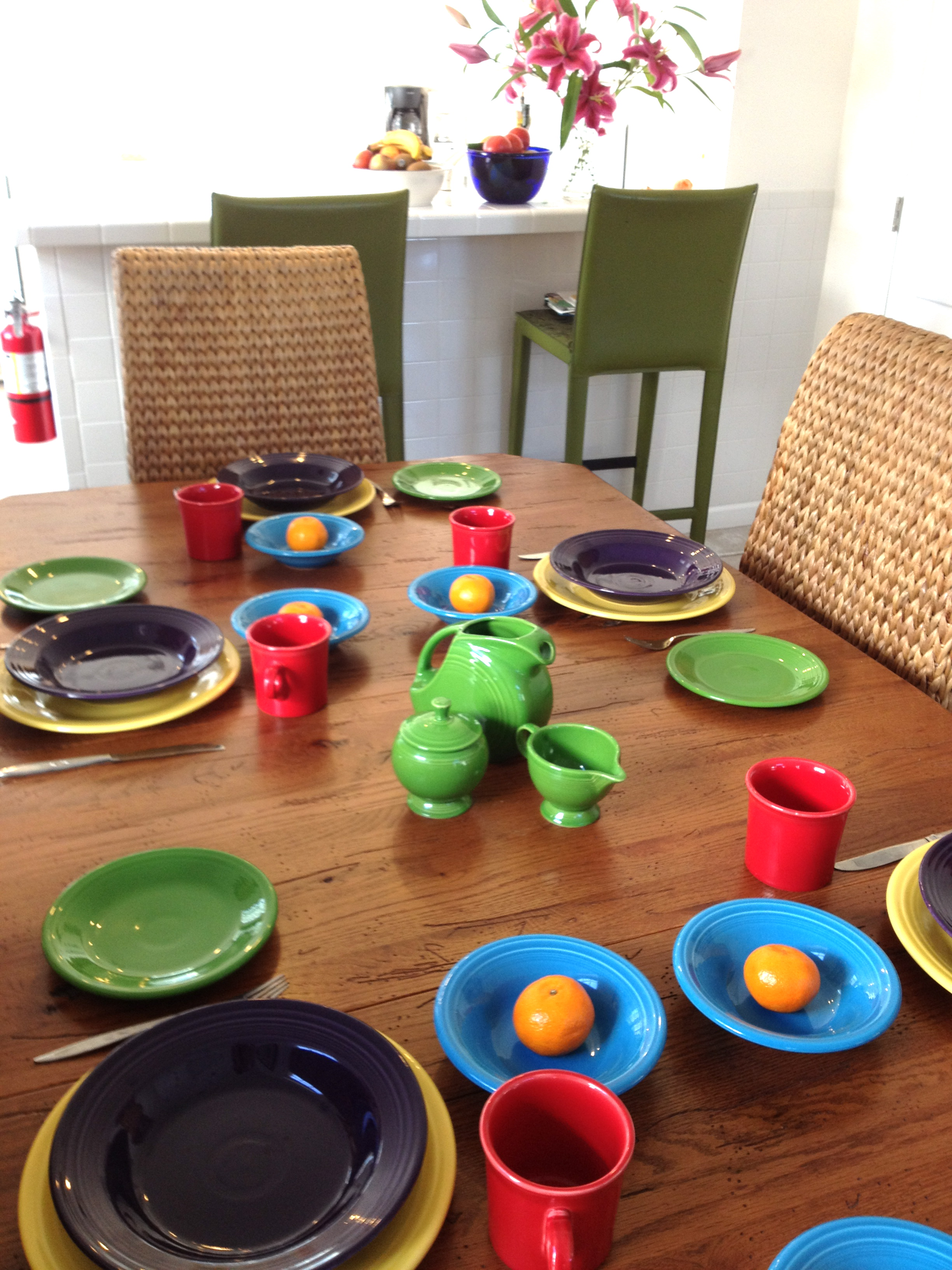 colorful diningware set by fiestaware on wooden dining table with wicker dining chairs for dining room decor ideas
