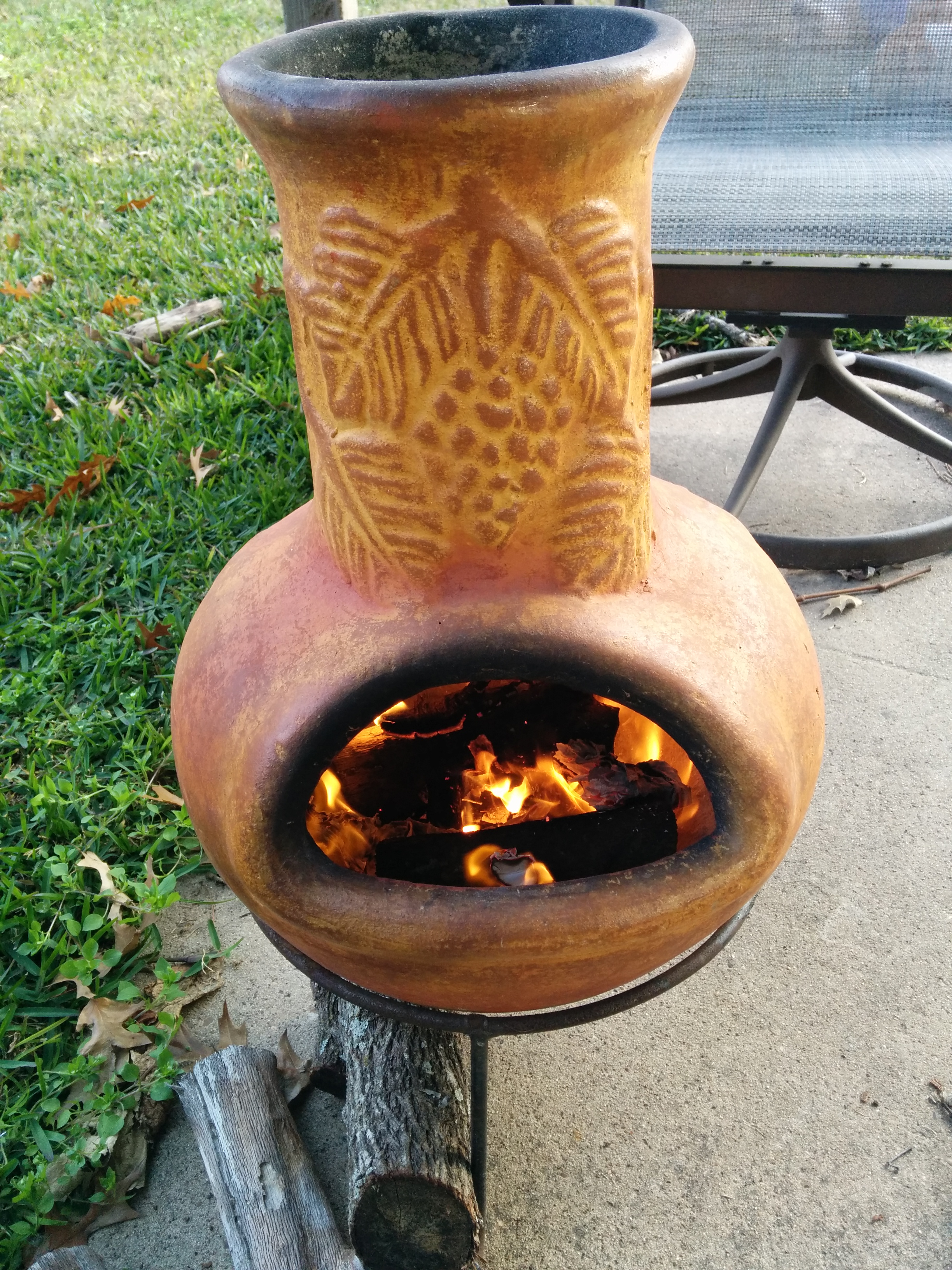 Cute Yellow Clay Chiminea Outdoor Fireplace With Leaves Ornament And Black Iron Stand For Outdoor Furniture Ideas