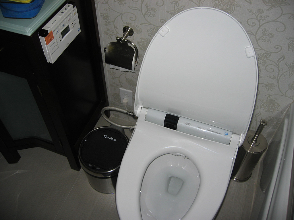 Toto Washlet S400 on white tile floor which matched with floral white wallpaper for bathroom decor ideas