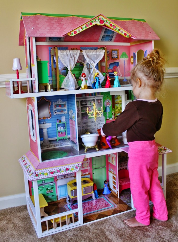 Wonderful Large Kidkraft Dollhouse In Triple Tier Design And Pink And White Theme Before The Yellow Wall Which Matched With Wooden Floor For Nursery Decor Ideas
