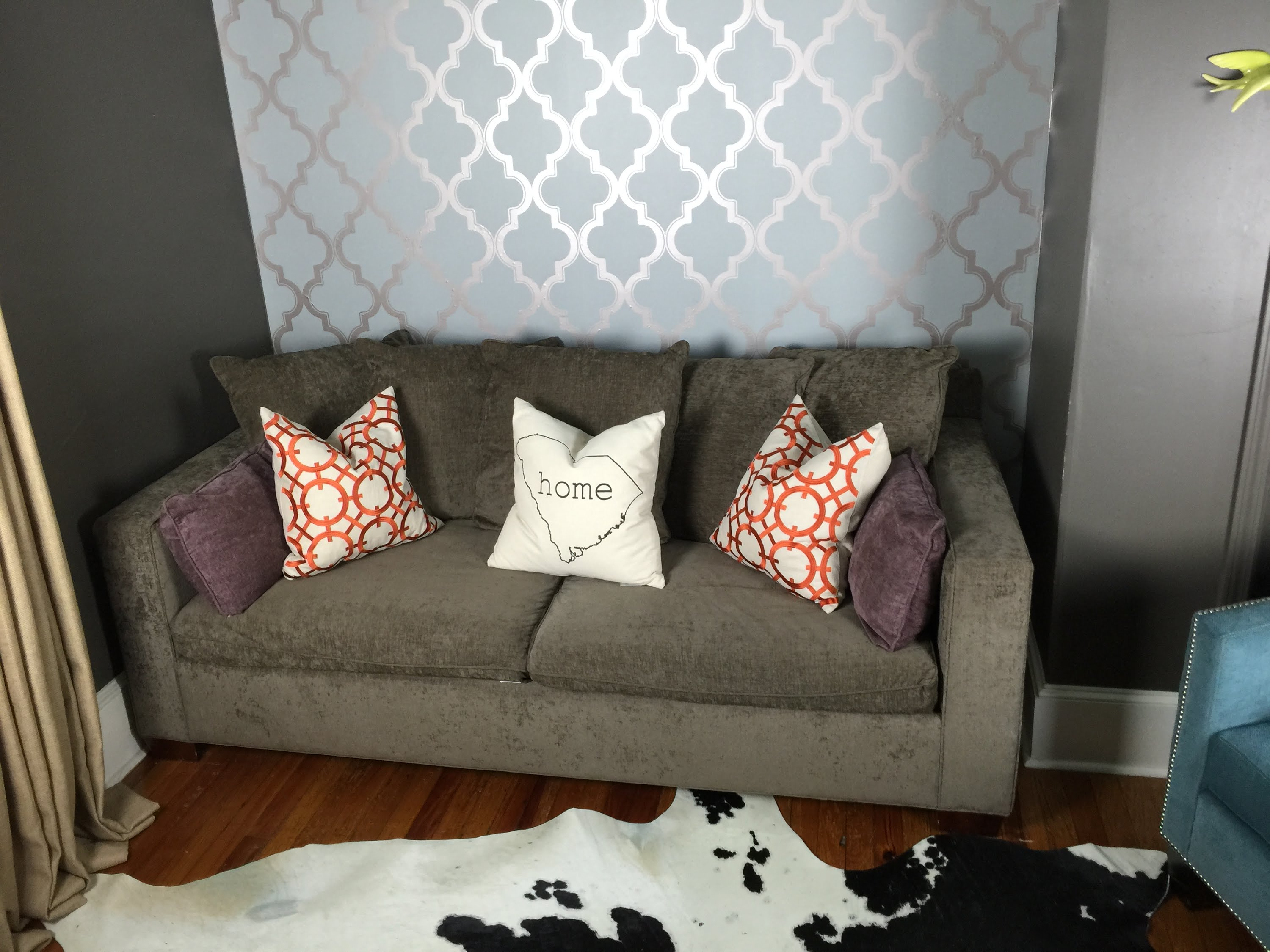 wonderful Tempaper Wallpaper matched with wooden floor plus gray sofa and cowhide pattern rug for living room decor ideas